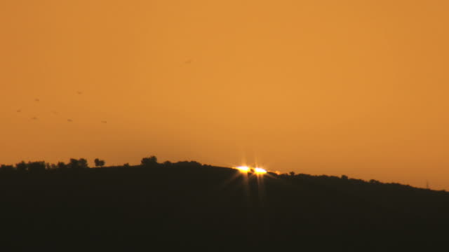 ms t/l shot of large sun rising behind horizotal mountain ridge with warm orange tones / israel - launch event stock videos & royalty-free footage
