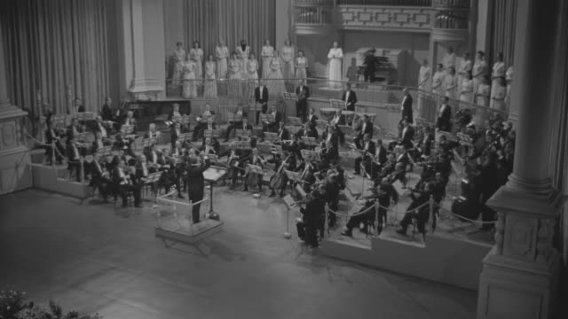 ms shot of large symphony orchestra and choir on stage - chorsänger stock-videos und b-roll-filmmaterial