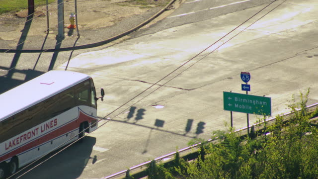 MS AERIAL Shot of large tour bus turns at sign for Highway 65 to Birmingham and Mobilev / Montgomery, Alabama, United States