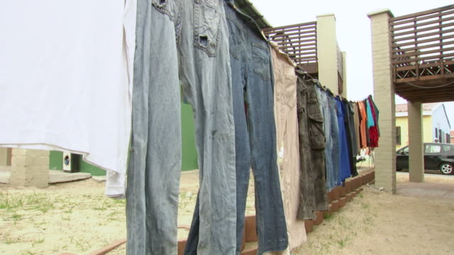 ws shot of laundry hanging on a clothes line to dry outside a sandbag house at freedom park township / cape town, south africa - clothesline stock videos & royalty-free footage