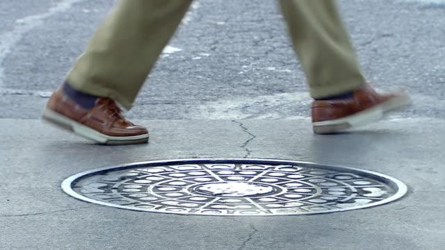 vídeos y material grabado en eventos de stock de cu shot of legs walking around sewer cap in street / new york, united states - part of a series