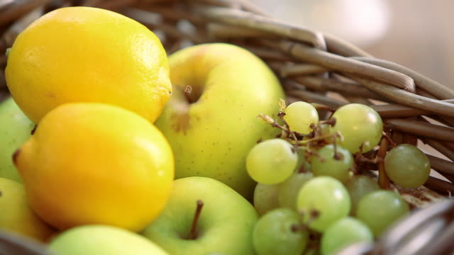 CU R/F Shot of lemons, grapes and apples in wooden fruit basket / Rome, Lazio, Italy