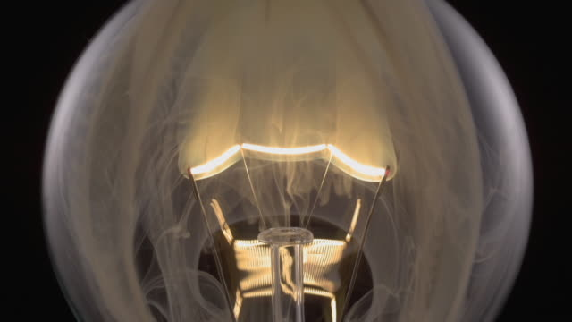 stockvideo's en b-roll-footage met ecu slo mo shot of light bulb, showing burning and smoking tungsten wire / munich, bavaria, germany - electric lamp