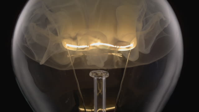 ecu slo mo shot of light bulb, showing burning and smoking tungsten wire / munich, bavaria, germany - glühbirne stock-videos und b-roll-filmmaterial