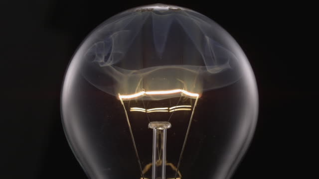 ecu slo mo shot of light bulb, showing burning and smoking tungsten wire / munich, bavaria, germany - super slow motion stock videos & royalty-free footage