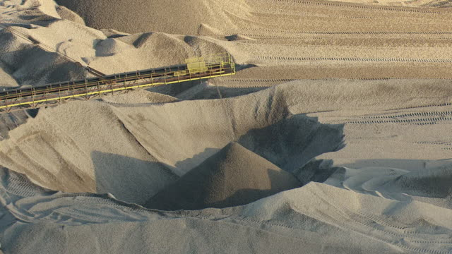cu aerial shot of limestone going through conveyer belt onto mound at limestone quarry at port of calcite / rogers city, michigan, united states - limestone stock videos and b-roll footage