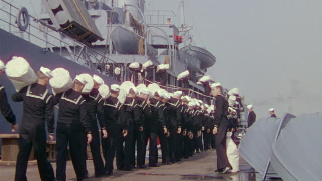 MS Shot of line of sailors in uniform and boarding ship