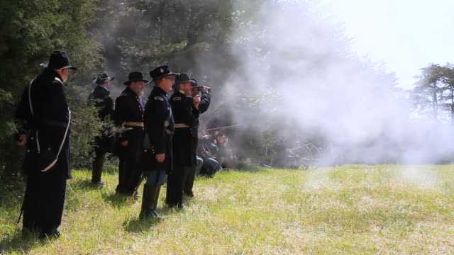 vídeos de stock e filmes b-roll de ms shot of line of union soldiers fire their rifles as commanders watch during battle / appomattox, virginia, united states - exército da união