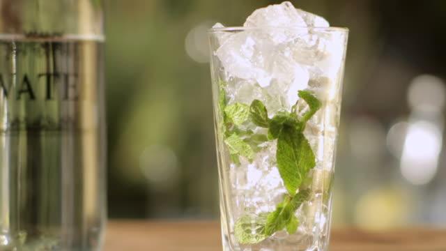 vídeos y material grabado en eventos de stock de cu shot of liquid poured into glass of ice and mint / south africa - mint leaf culinary