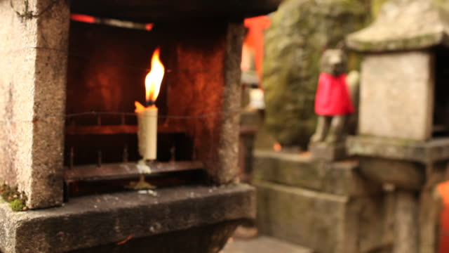 ms r/f shot of lit candle in front of colorful shrines / kyoto, kanto, japan - ローソク点の映像素材/bロール