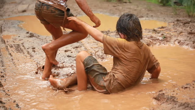 ms td shot of little boy and little girl taking mud baths together and playing in muddy water / montezuma, punteranes, costa rica - schlamm stock-videos und b-roll-filmmaterial