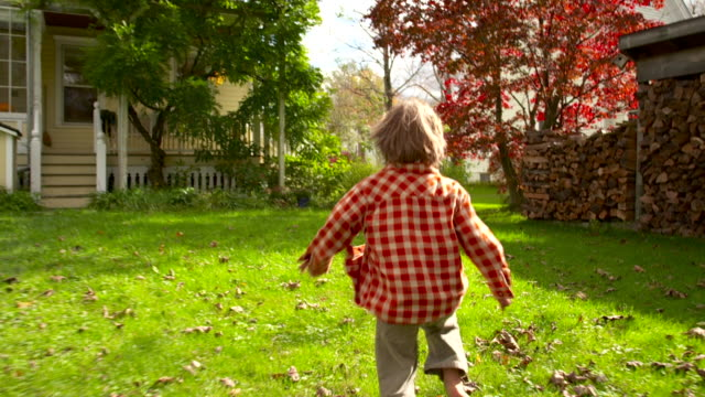 ws slo mo ts shot of little boy running through yard / tivoli, new york, united states - hausgarten stock-videos und b-roll-filmmaterial