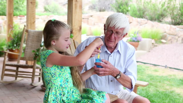 ms shot of little girl blowing bubbles with her grandfather / lamy, new mexico, united states - human age stock videos & royalty-free footage