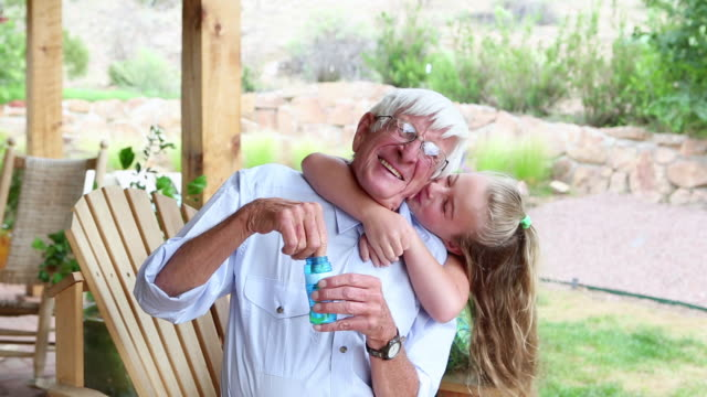 ms shot of little girl blowing bubbles with her grandfather / lamy, new mexico, united states - enkelin stock-videos und b-roll-filmmaterial