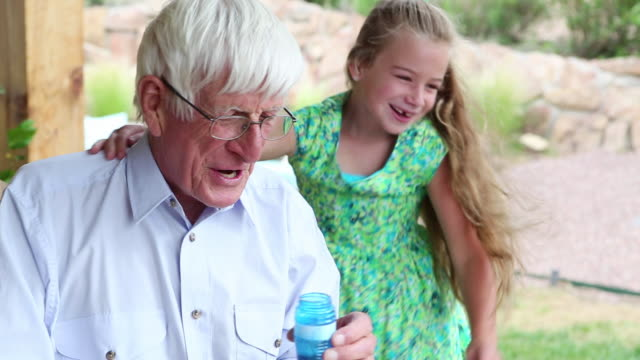ms shot of little girl blowing bubbles with her grandfather / lamy, new mexico, united states - grandfather stock videos & royalty-free footage