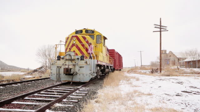 ms pan shot of little girl coming down on train in snow / lamy, new mexico, united states - nur mädchen stock-videos und b-roll-filmmaterial