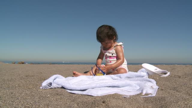ms shot of little girl drinking orange juice on beach / marbella, andalusia, spain - sonnenschild stock-videos und b-roll-filmmaterial