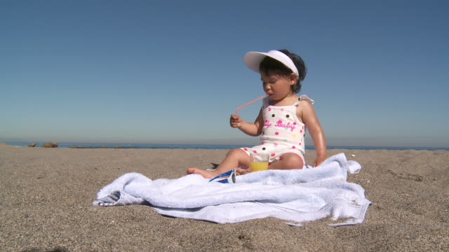 ms shot of little girl drinking orange juice with straw / marbella, andalusia, spain - sun visor stock videos & royalty-free footage