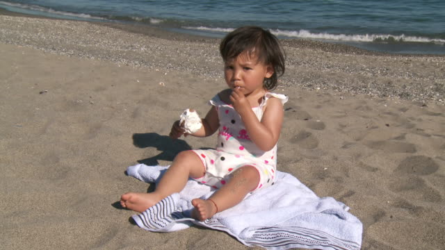 MS Shot of little girl eating ice cream cone on beach / Marbella, Andalusia, Spain