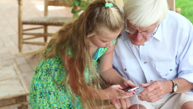 ms r/f shot of little girl helping her grandfather use ipod / lamy, new mexico, united states - mp3プレイヤー点の映像素材/bロール
