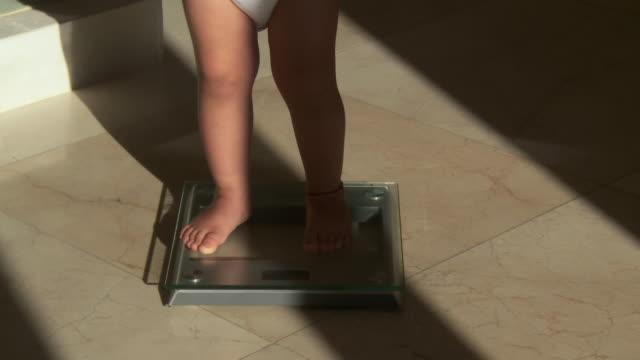 cu shot of little girl weighing on bathroom scale / marbella, andalusia, spain - 体重計点の映像素材/bロール