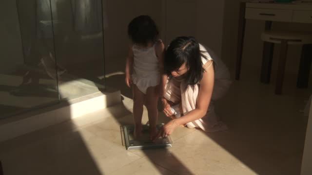shot of little girl weighing on bathroom scale. - 体重計点の映像素材/bロール