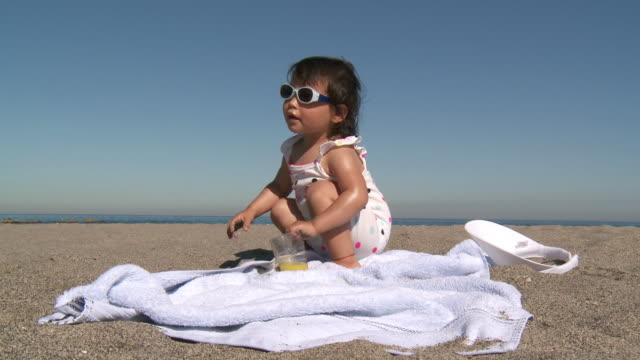 ms shot of little girl with sunglasses drinking orange juice on beach / marbella, andalusia, spain - saft stock-videos und b-roll-filmmaterial