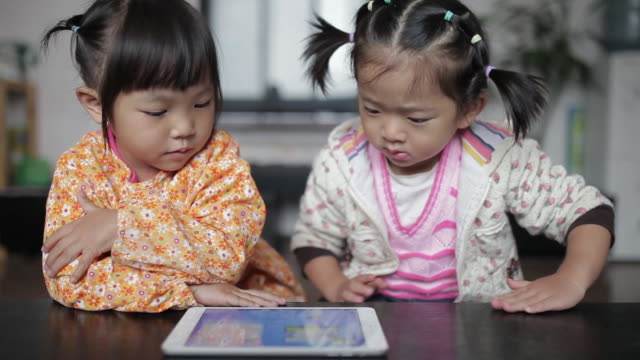 CU Shot of Little girls playing games with digital tablet computer in home / Xi'an, Shaanxi, China