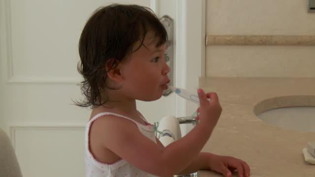cu shot of little metis girl is brushing her teeth in bathroom / marbella, andalusia, spain - endast en flickbaby bildbanksvideor och videomaterial från bakom kulisserna