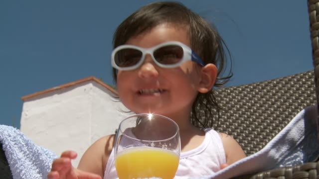 cu la shot of little metis girl with sunglasses drinking orange juice / marbella, andalusia, spain - juice drink stock videos & royalty-free footage