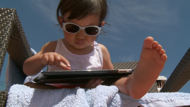 cu la shot of little metis girl with sunglasses playing with digital tablet / marbella, andalusia, spain - babies only stock videos & royalty-free footage