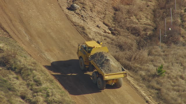 cu aerial ts shot of loaded truck moving at landfill (outside fairmont mill) / south carolina, united states - baustelle stock-videos und b-roll-filmmaterial