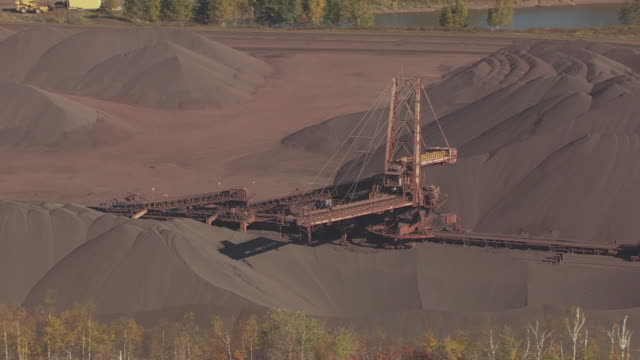 MS AERIAL Shot of loader machine in piles of ore / Minnesota, United States