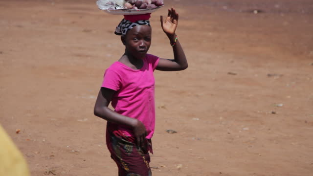 ms ts shot of local girl walking and local life with children / freetown, sierra leone - 運ぶ点の映像素材/bロール