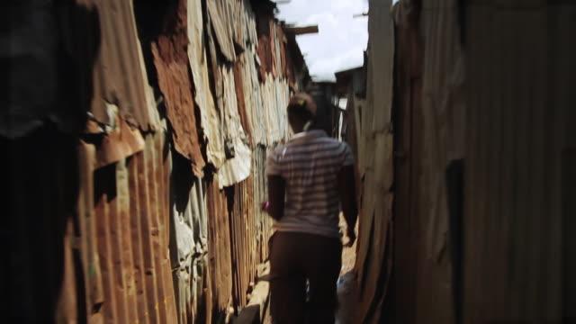 vídeos de stock e filmes b-roll de ms shot of local girl walking between houses and local life / freetown, sierra leone - pobreza questão social