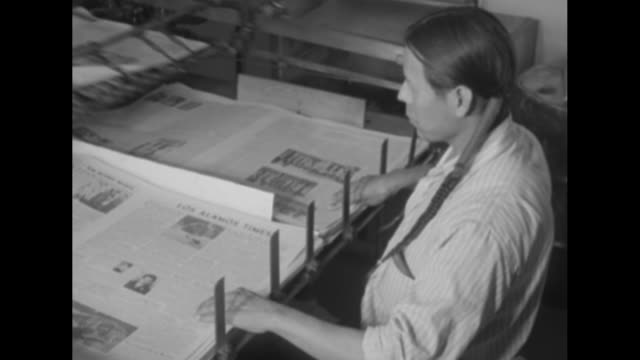 vídeos de stock, filmes e b-roll de shot of local newspaper los alamos times being printed in printing press / pueblo indian stacking copies of newspaper as they roll out of press / two... - anasazi