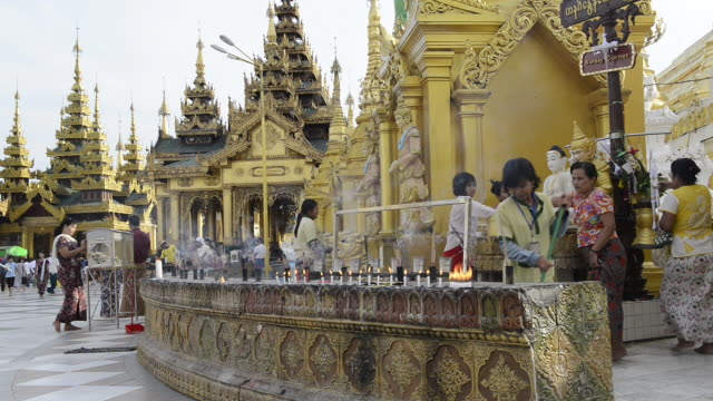 ws shot of local people pouring water on buddha likeness and candles and incense burning in shwedagon pagoda / yangon, yangon division, myanmar - male likeness stock videos & royalty-free footage