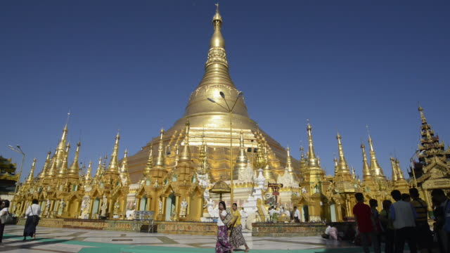 ms shot of local people walking around golden stupa of famous shwedagon pagoda / yangon, yangon division, myanmar - stupa stock videos & royalty-free footage