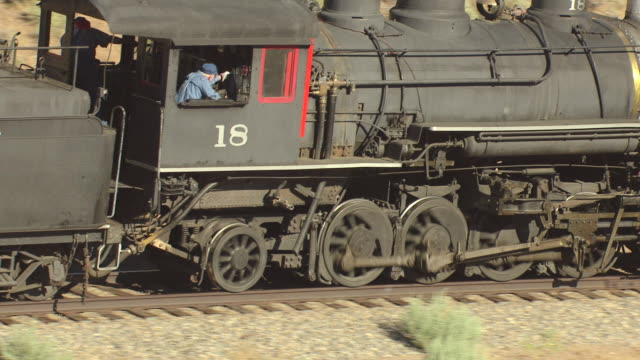 CU AERIAL Shot of locomotive Virginia and Truckee Railroad train and with passengers riding / Nevada, United States