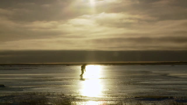 ws shot of lone hockey player with stick handles skating on ice with shining sun / arviat, nunavut, canada - wiese stock videos & royalty-free footage