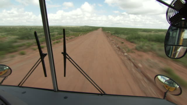 ms pov shot of looking out from windshield as bus drives down dirt road / roswell, new mexico, united states - roswell stock videos & royalty-free footage