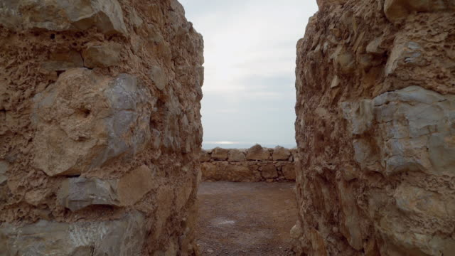 ms shot of looking through ancient ruins at masada and dead sea in distance at negev desert / israel - negev stock videos & royalty-free footage
