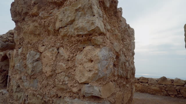 ms pan shot of looking through ancient ruins at masada and dead sea in distance at negev desert / israel - old ruin stock videos & royalty-free footage