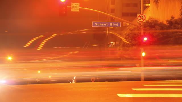 ms t/l shot of los angeles at night sunset blv street sign with streaking traffic / los angeles, california, united states - västerländsk text bildbanksvideor och videomaterial från bakom kulisserna
