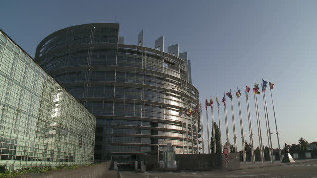 ms shot of louise weiss european parliament building with flags swaying  on breeze / strasbourg, alsace, france - french culture stock videos & royalty-free footage