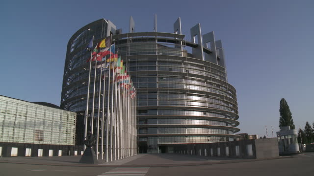 ms shot of louise weiss european parliament building with flags swaying  on breeze / strasbourg, alsace, france - straßburg stock-videos und b-roll-filmmaterial