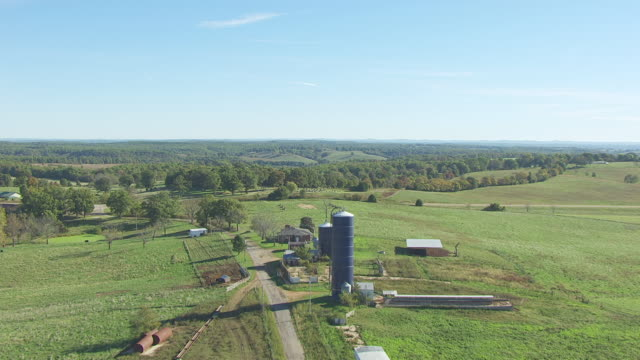 ms aerial td shot of low approaching hill and birds eye view over farm silo / missouri, united states - country road stock videos & royalty-free footage
