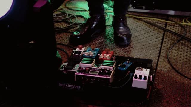 vídeos y material grabado en eventos de stock de disparo de músico de sección baja en el escenario empujando en el pedal de efecto de la guitarra - pedal