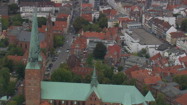 ms aerial shot of lubeck cathedral with streets and houses rooftops / germany - lübeck stock-videos und b-roll-filmmaterial