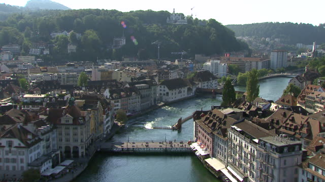 ms aerial shot of lucerne with kapellbrucke over reuss river with river is flank by jesuit church and musegg wall / lucerne, switzerland - schweiz stock-videos und b-roll-filmmaterial